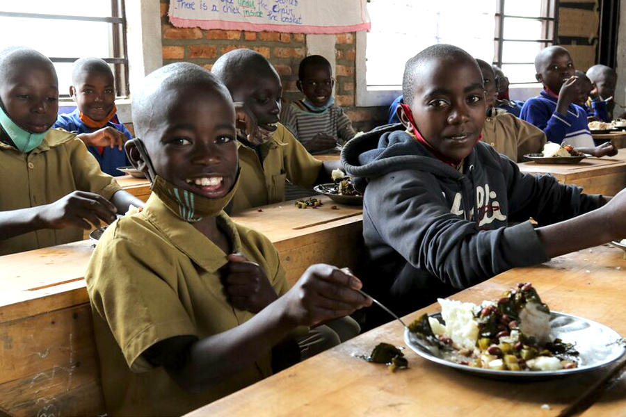 Donat, aged 9, enjoys a WFP-supplied school meal with classmates. Photo: WFP/Emily Fredenberg