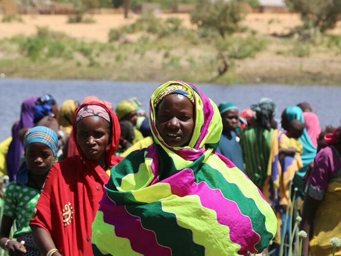 women on river bank